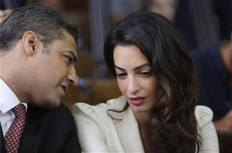 Canadian Al-Jazeera English journalist Mohammed Fahmy, left, talks to human rights lawyer Amal Clooney before his verdict in a courtroom in Tora prison in Cairo, Egypt, Saturday, Aug. 29, 2015. AP