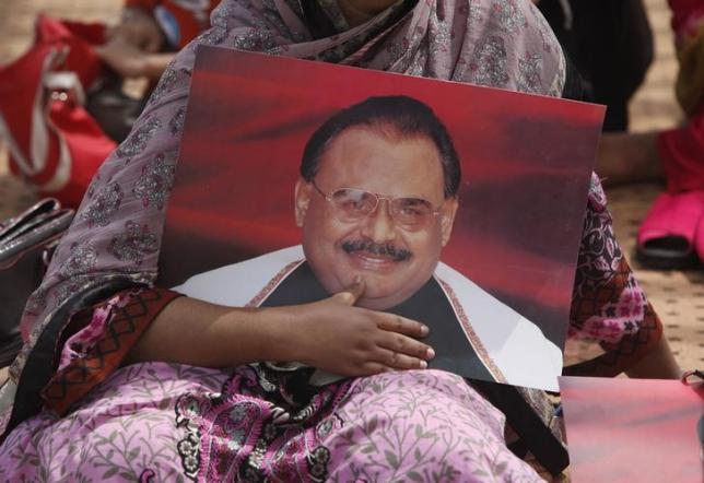 A supporter of Pakistan's Muttahida Quami Movement (MQM) political party, holds a poster of Altaf Hussain at a gathering to show solidarity with their leader in Karachi June 4, 2014. REUTERS/Akhtar Soomro