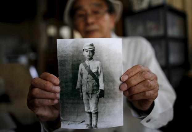 Yoshiteru Kohata, a 86-year-old Nagasaki atomic bombing survivor and retired school teacher, who returned to his home region of Fukushima after World War Two, poses with a portrait taken when he was in middle school, at his home in the town of Miharu, Fukushima Prefecture,...nPhoto: Reuters/Toru Hanai