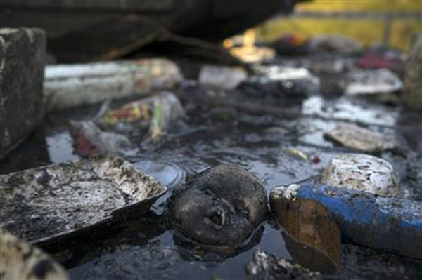 A doll's head floats in the polluted waters of a canal at the Mare slum complex in Rio de Janeiro, Brazil, Friday, July 31, 2015. In Rio, much of the waste runs through open-air ditches to fetid streams and rivers that feed the Olympic water sites and blight the city's picture postcard beaches.  Photo:AP