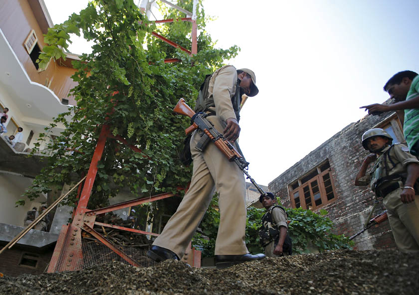 Indian Central Reserve Police Force (CRPF) personnel inspect the site of a grenade attack next to a telecom tower in Srinagar, July 24, 2015. On Friday, three attacks were carried out on telecoms facilities in the Muslim-majority state's summer capital of Srinagar, one of them near the office of Chief Minister Mufti Mohammad Sayeed. Photo: Reuters