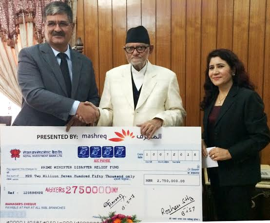 Prime Minister Sushil Koirala shake hands with Khursheed Anwar, Director of the Mashreq Bank of the United Arab Emirates while receiving a cheque worth Rs 2.7 million as a relief amount for the quake survivors at his official residence in Baluwatar on Sunday, August 16, 2015. Photo: PM's Secretariat