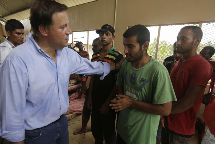 Panama's President Juan Carlos Varela, left, talks with a a migrant from Nepal during a visit to a shelter in Meteti, Panama, Monday, Aug. 17, 2015. President Varela announced Monday the construction of a shelter for migrants that enter on foot from the Colombian border to Panama. (AP Photo/Arnulfo Franco)