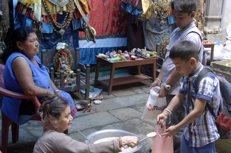 Buddhist devotees receive offerings during Pancha Daan festival in Lalitpur, on Sunday. Pancha Daan, the festival of five summer gifts, is observed by Buddhists who give away wheat grains, rice grains, salt, money and fruit. Photo: Naresh Shrestha/ THT