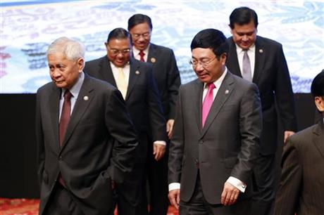 Philippine Foreign Secretary Albert del Rosario, front left, walks with Vietnam's Foreign Minister Pham Binh Minh, front right, after they pose for a family photograph during the Association of Southeast Asian Nations (ASEAN) Foreign Ministers Meeting plenary session in Kuala Lumpur, Malaysia on Tuesday, Aug. 4, 2015. AP