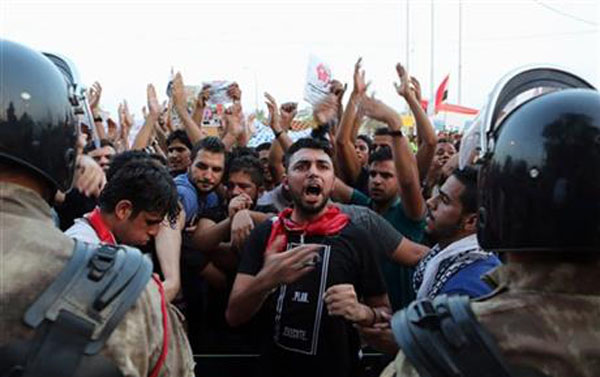 Protesters chant anti-government slogans while riot police guard the provincial council building during a protest against corruption and the lack of government services and power outage in Basra, 340 miles (550 kilometers) southeast of Baghdad, Iraq, Friday, Aug. 7, 2015. Photo:AP