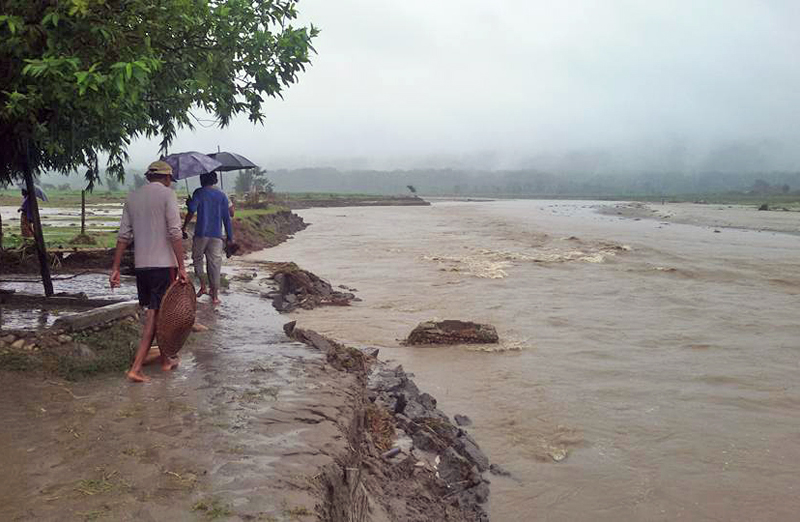 Men walking on the banks of the swollen Rieu River following incessant rainfall at Madi, Chitwan, on Friday.  Photo:THT