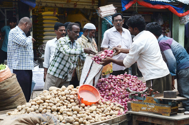 People buying onions at Rythu Bazaar produce market, in Hyderabad, on Wednesday. Vegetable prices have risen by up to 67 percent due to tight supplies at wholesale markets due to heavy monsoon rains. Photo: AFP