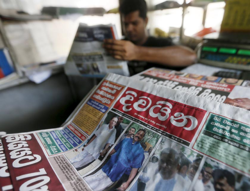 A newspaper front page with a picture of former president Mahinda Rajapaksa is displayed as a man reads its contents at a newsstand in Colombo August 18, 2015. Photo: Reuters