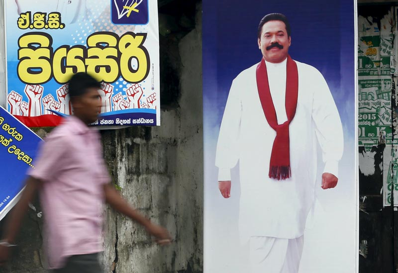 A man walks past a poster of Sri Lanka's former president Mahinda Rajapaksa ahead of a general election, in Galle August 14, 2015. Photo: Reuters