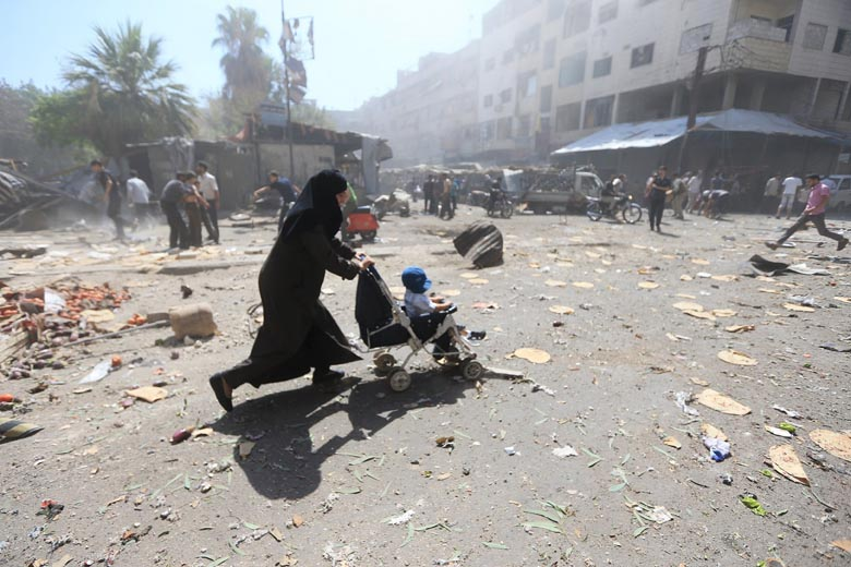 A woman pushes a baby stroller as she rushes away after what activists said were airstrikes by forces loyal to Syria's President Bashar al-Assad on a busy marketplace in the Douma neighborhood of Damascus, Syria August 12, 2015.  Photo: Reuters