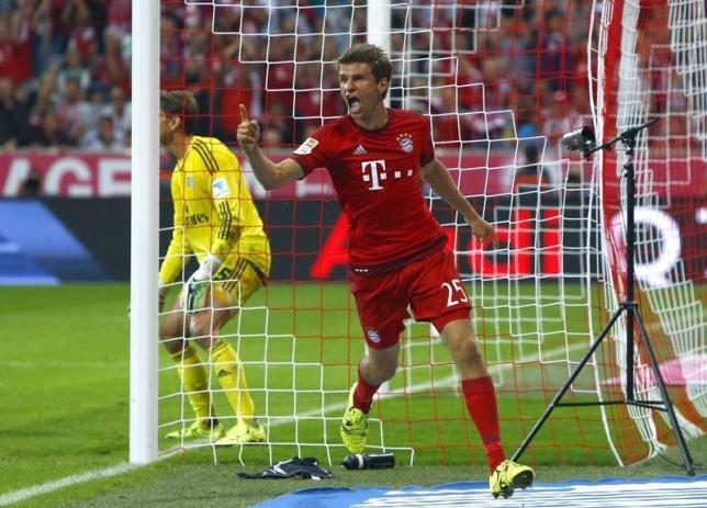 Bayern Munich's Thomas Mueller celebrates after scoring a goal past Hamburger SV's goalkeeper Rene Adler (L) during their Bundesliga, German first division soccer match in Munich, Germany August 14, 2015. REUTERS/Michaela Rehle