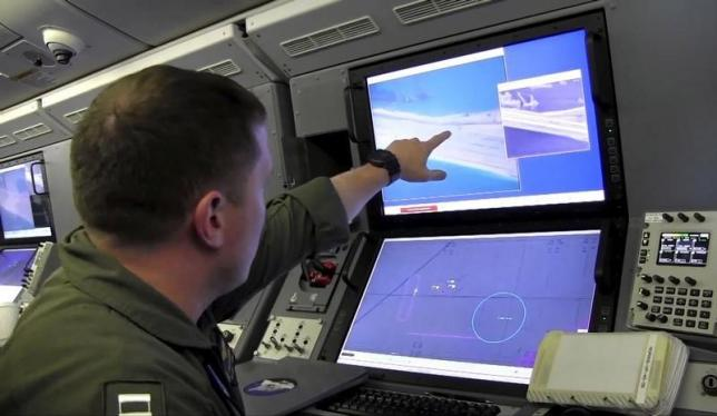 A US Navy crewman aboard a P-8A Poseidon surveillance aircraft views a computer screen purportedly showing Chinese construction on the reclaimed land of Fiery Cross Reef in the disputed Spratly Islands in the South China Sea in this still image from video provided by the United States Navy May 21, 2015. REUTERS/U.S. Navy/Handout via Reuters