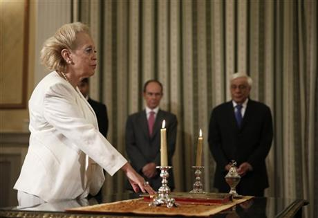 Vassiliki Thanou, 65, take a religious oath during a swearing in ceremony at the Presidential Palace in Athens, on Thursday, Aug. 27, 2015, to become Greece's first female prime minister. AP