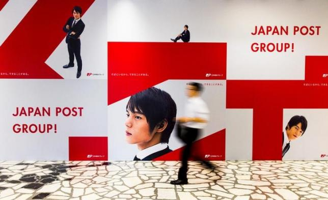 A man walks past an advertising poster in the headquarters of Japan Post in Tokyo June 26, 2015. REUTERS/Thomas Peter/Files