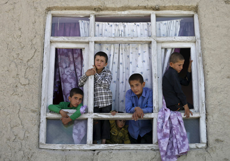 Children look out from the broken window of a house near the site of a car bomb blast at the entrance gate to Kabul airport, Afghanistan August 10, 2015. A car bomb exploded near the entrance to Kabul airport on Monday, killing at least four people and wounding 17, days after a series of suicide attacks in the Afghan capital killed dozens and wounded hundreds. Photo: Reuters