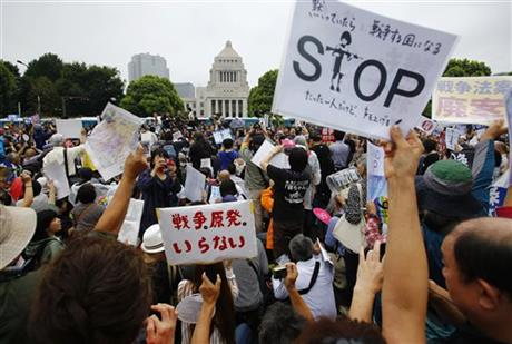 Protesters hold anti-war placards in front of the National Diet building during a rally in Tokyo, Sunday, Aug. 30, 2015.  AP