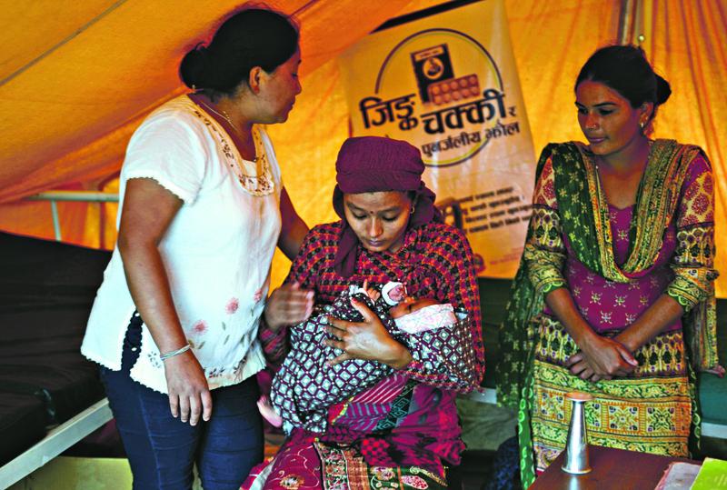 Junu Shrestha (centre) holding her child as nshe sits at a makeshift nbirthing centre in the village nof Gerkhu nin Nuwakot. Photo: AFP