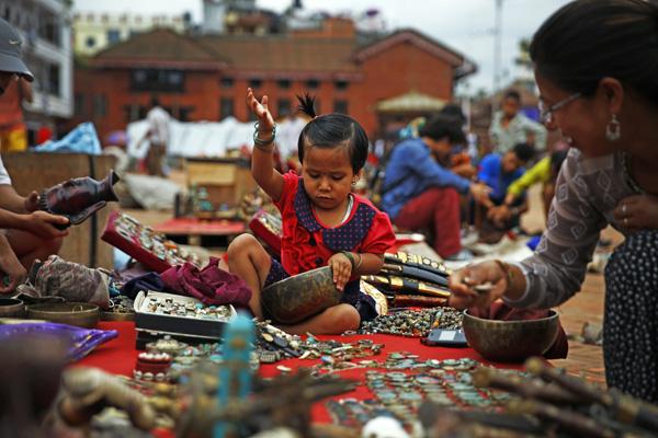 A child helping arrange goods at a street shop in Basantapur, Kathmandu, on Friday. Photo:THT