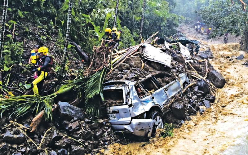 This image released by the New Taipei Fire Department shows emergency nrescue workers carrying children passing cars crushed by a mudslide caused by Typhoon Soudelor in Xindian, New Taipei City, in Taiwan, on Saturday. Photo: AP