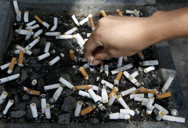 A smoker places a cigarette stub on a tray filled with stubs beside a road in Las Pinas city, Metro Manila August 7, 2015. Photo: Reuters