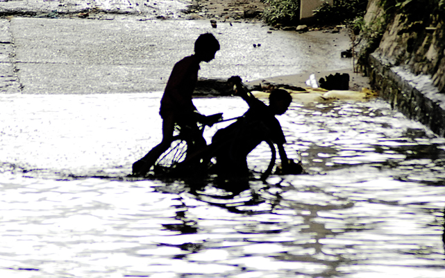 Two youths who fell from a bicycle while crossing the flooded Bagmati bridge underpass, struggle to lift up the bicycle at Kupondole, in Lalitpur, on Saturday. Photo: THT