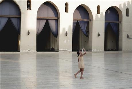 A girl drinks water inside the Al-Hakim bi-Amr Allah Mosque on Al Muezz street in Cairo, Egypt, Thursday, Aug. 13, 2015. AP