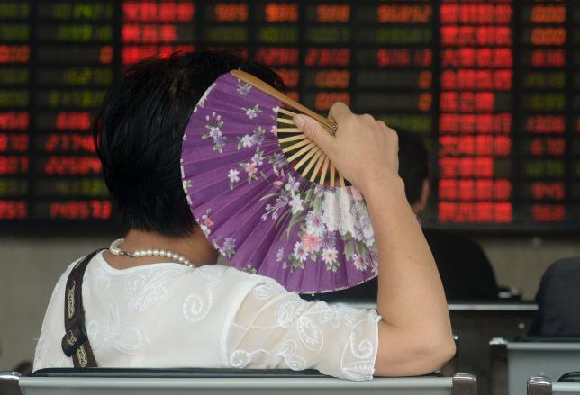 An investor holds a fan as she looks at stock information on an electronic board at a brokerage house in Shanghai, August 26, 2015. REUTERS/China Daily