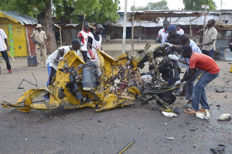 People inspect a damaged tricycle at the site of a bomb explosion in Maiduguri, Nigeria, Friday, July 31, 2015 . A woman suicide bomber killed many people at a crowded market early Friday in a blast that thundered across the northeastern Nigerian city of Maiduguri, witnesses said.  Photo: AP