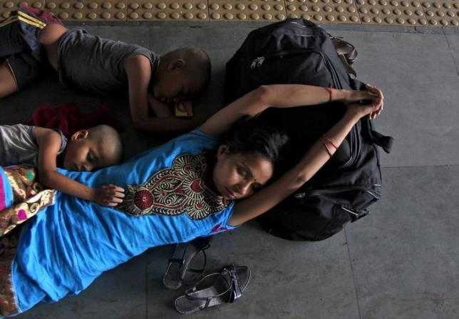 A passenger sleeps along with her children at a railway station on a hot summer day in Allahabad, May 26, 2015. REUTERS/Jitendra Prakash/Files