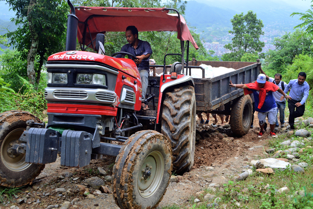 People pushing a tractor that got stuck in a muddy road while heading to Manungkot-7 of Byas Municipality in  Tanahun district on Friday, August 7, 2015. Photo: Madan Wagle