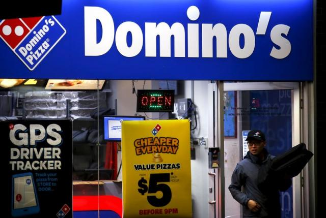 A worker carries a pizza for delivery as he exits a Domino's pizza store in Sydney, Australia, August 12, 2015.  Photo: REUTERS/David Gray