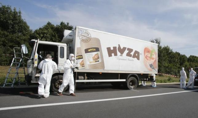 Forensic police officers inspect a parked truck in which up to 50 migrants were found dead, on a motorway near Parndorf, Austria August 27, 2015. Photo:   REUTERS