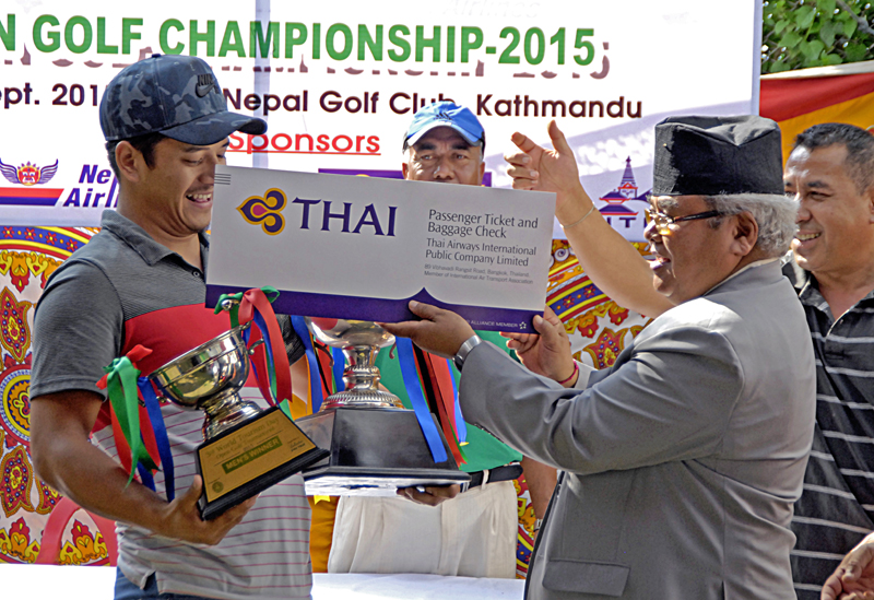 Phuntosok N Lama receives the trophy from Civil Aviation and Tourism Minister Kripasur Sherpa after the third World Tourism Day Golf Championship on Sunday. Photo: THT