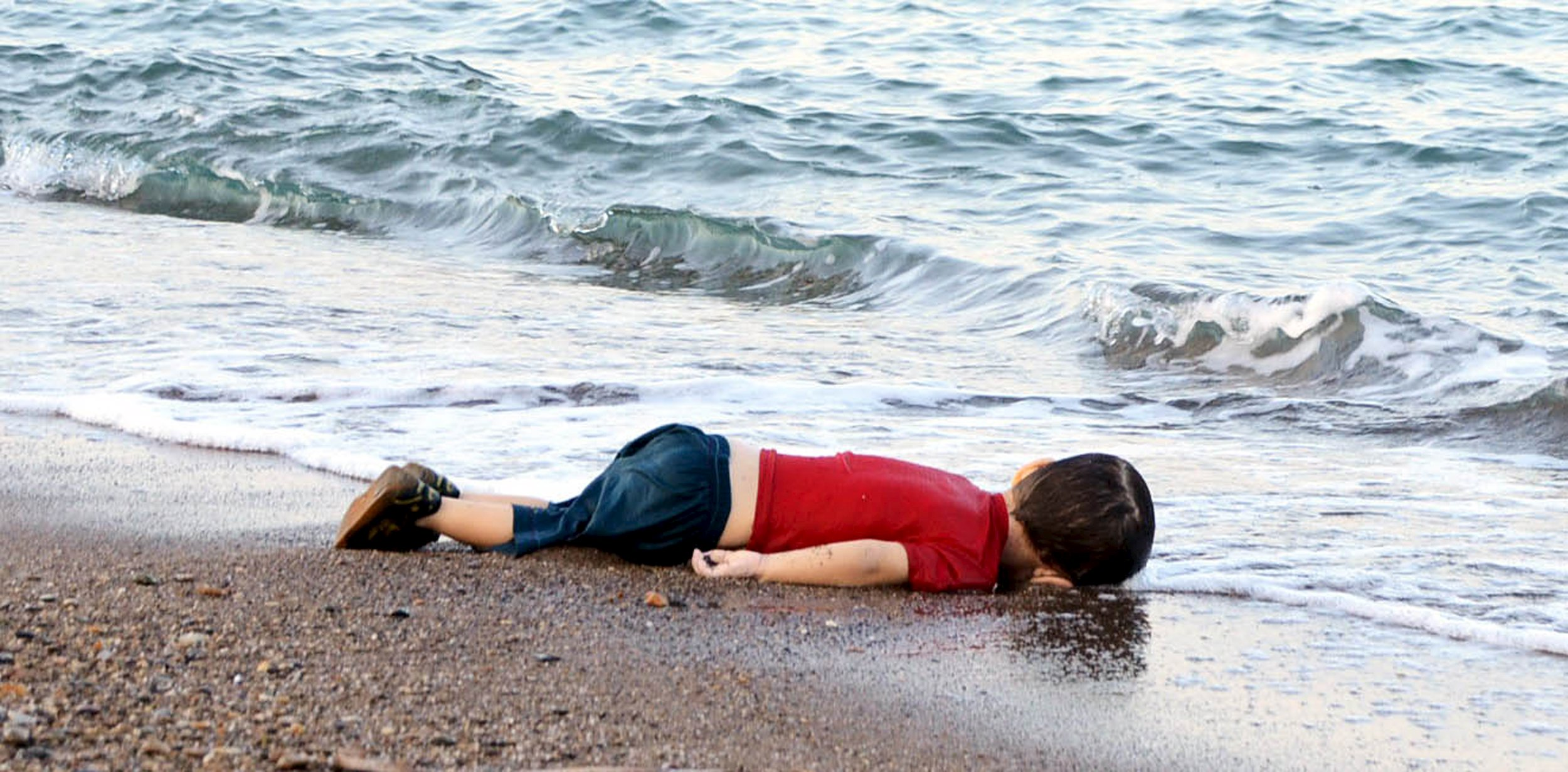 A young migrant, who drowned in a failed attempt to sail to the Greek island of Kos, lies on the shore in the Turkish coastal town of Bodrum, on Wednesday.  Photo: Reuters