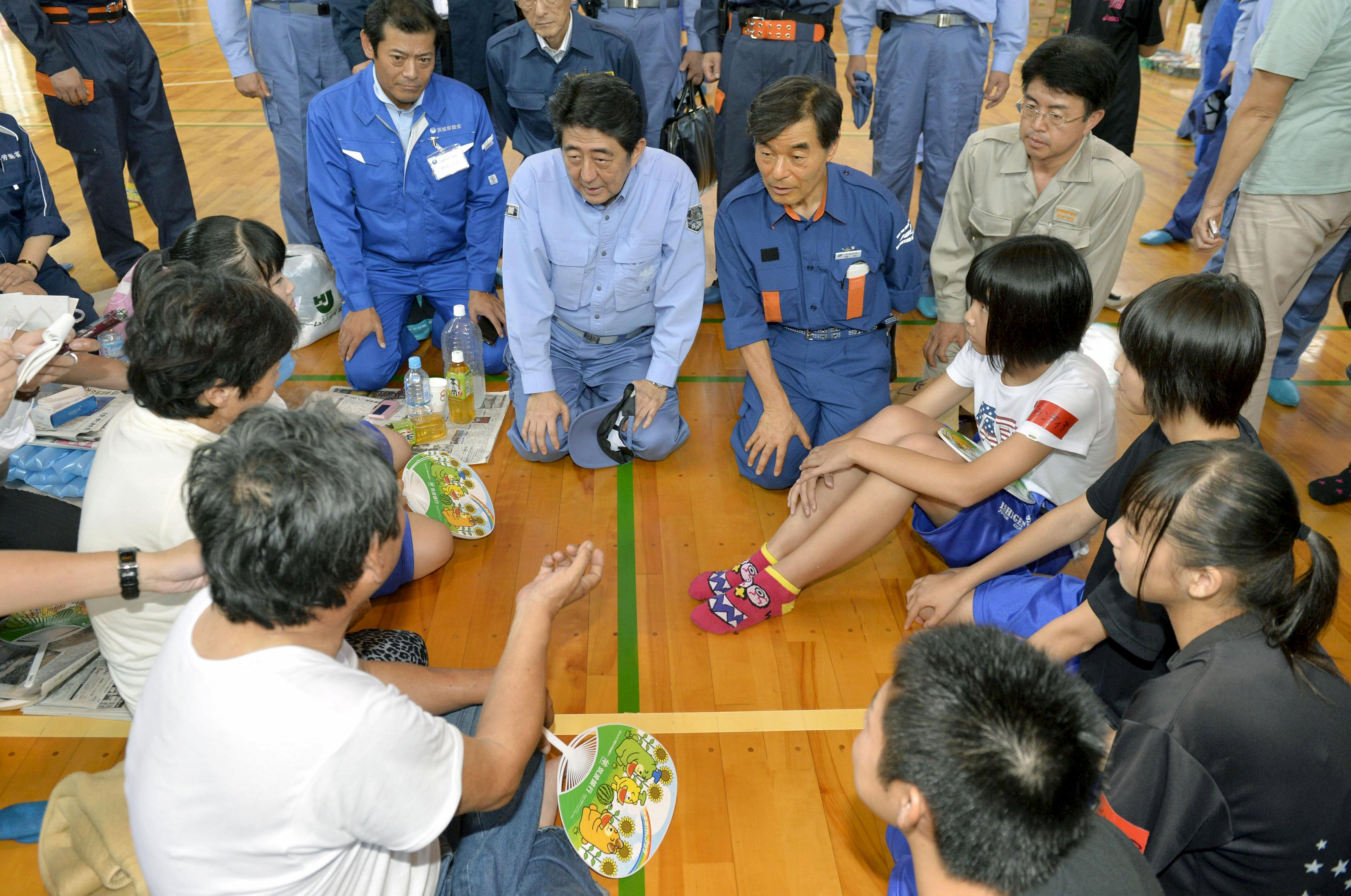 Japan's Prime Minister Shinzo Abe (top C) talks with evacuees from an area flooded by the Kinugawa river, caused by typhoon Etau, at an evacuation center in Joso, Ibaraki prefecture, Japan, in this photo taken by Kyodo September 12, 2015. Floods that swept houses off foundations and crushed them under landslides spread across Japan on Friday as more rivers burst their banks, leaving at least 23 people missing and forcing more than 100,000 to flee.   Mandatory credit REUTERS/Kyodo ATTENTION EDITORS - FOR EDITORIAL USE ONLY. NOT FOR SALE FOR MARKETING OR ADVERTISING CAMPAIGNS. THIS IMAGE HAS BEEN SUPPLIED BY A THIRD PARTY. IT IS DISTRIBUTED, EXACTLY AS RECEIVED BY REUTERS, AS A SERVICE TO CLIENTS. MANDATORY CREDIT. JAPAN OUT. NO COMMERCIAL OR EDITORIAL SALES IN JAPAN.
