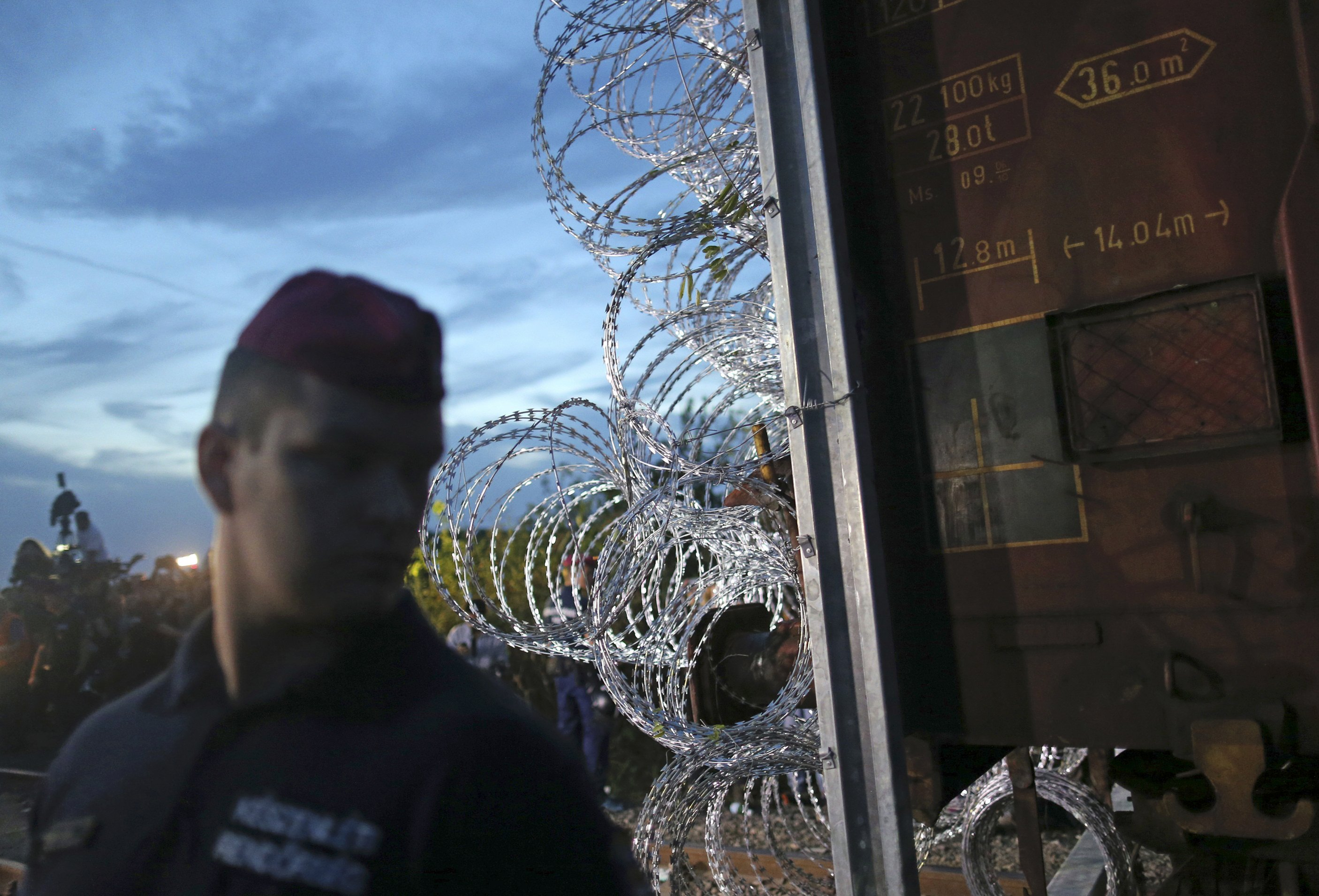 A Hungarian policeman stands guard as a freight train wagon is used to seal the border fence with Serbia near the village of Roszke, Hungary, September 14, 2015. Hungary has closed off a railway track used by tens of thousands of migrants to enter the European Union on foot, launching a crackdown promised by the right-wing government to tackle Europe's worst refugee crisis in two decades.      REUTERS/Dado Ruvic