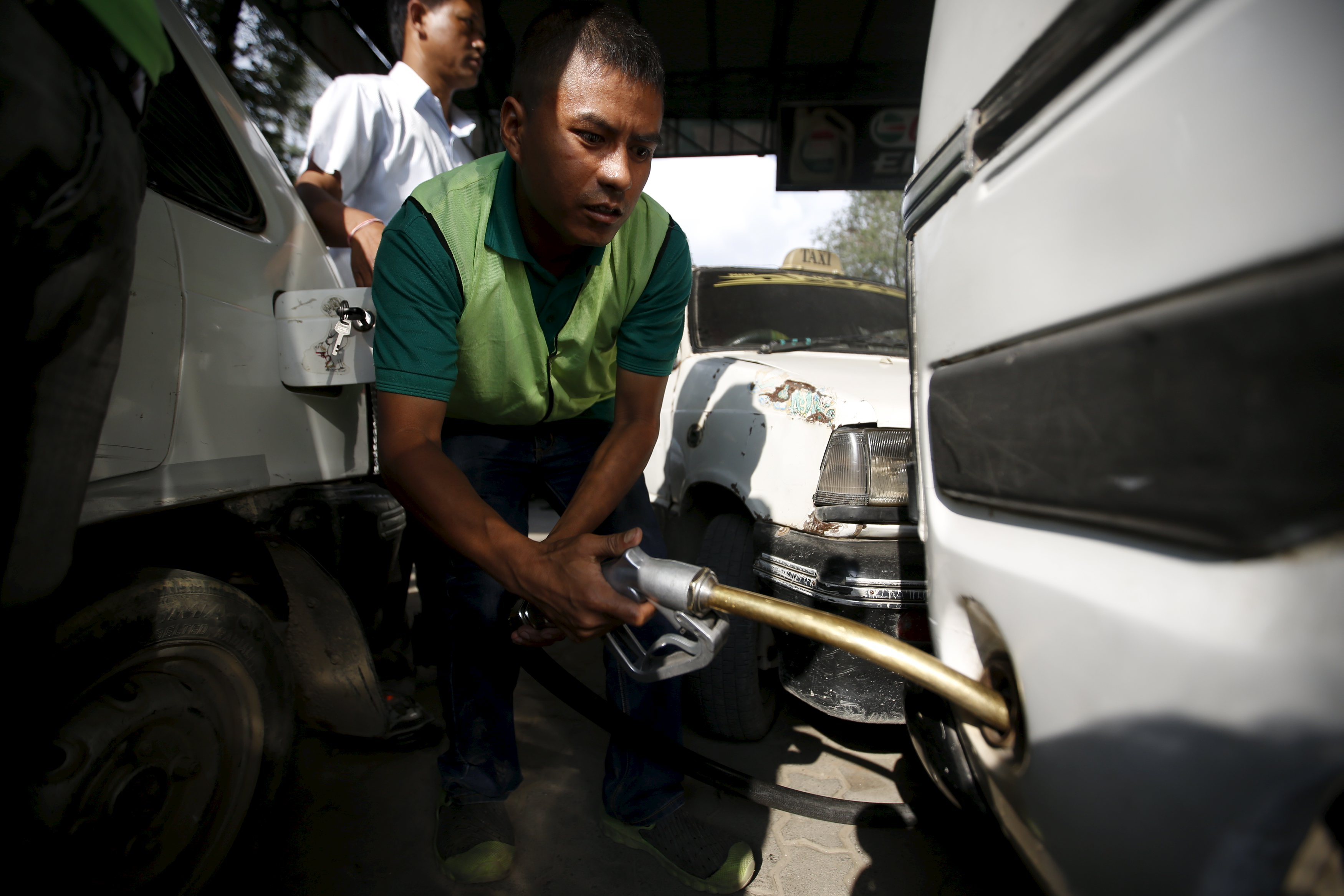 A worker refills petrol on a vehicle at a fuel station in Kathmandu on September 28, 2015. Photo: Reuters/File