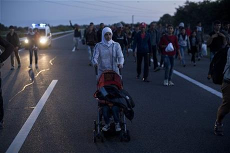 A woman pushes a stroller as she walks on the highway close to Roszke, Hungary, Monday, Sept. 7, 2015. Several hundred Arabs, Asians and Africans tired of waiting for buses broke through Hungarian police lines near the Serbian border Monday and marched north on the main highway towards Budapest as authorities once again demonstrated an inability to control the human tide passing through Hungary. Photo: AP