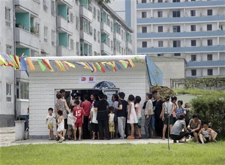 In this Aug. 16, 2015 photo, people queue up at kiosk in Pyongyang, North Korea. Street stalls that offer North Koreans a place to spend - or make - money on everything from snow cones to DVDs are flourishing in Pyongyang and other North Korean cities, modest but growing forms of private commerce in a country where capitalism is officially anathema. Photo: AP