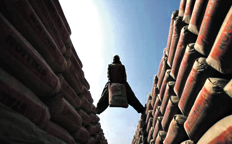 A labourer moves sacks of cement