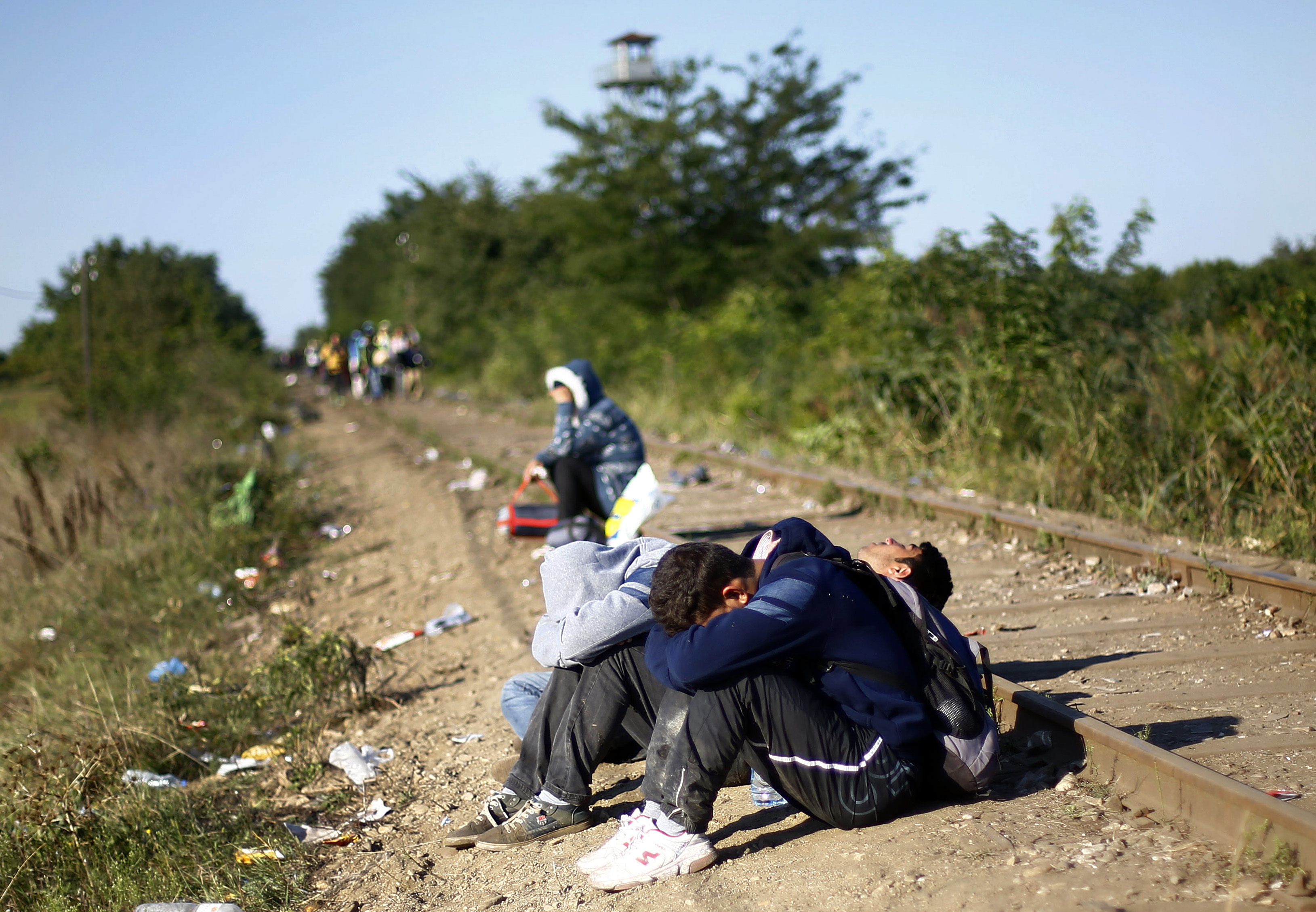 Migrants rest by the railway track near Roszke, southern Hungary, Wednesday, Sept. 9, 2015. Migrants anxious to pass through Hungary towards central Europe are making their way on foot at Hungary's southern border with Serbia. Photo: AP