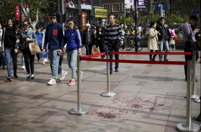 People walk by an area where two people were injured in a knife-wielding attack near People's Square in central Shanghai April 17, 2015. REUTERS/Carlos Barria