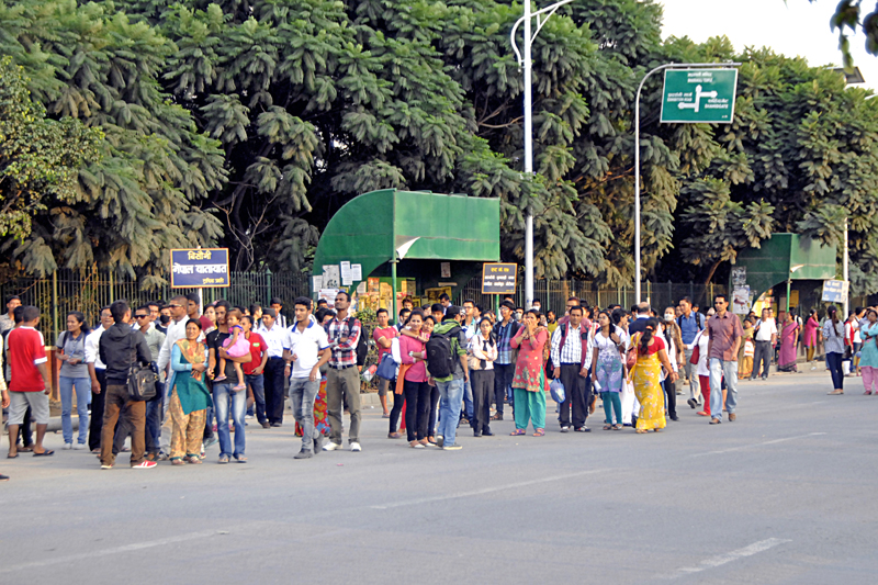 Commuters waiting for public vehicles to reach their respective destinations at Bhrikutimandap, in Kathmandu, on Monday. Photo: THT