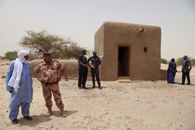 FILE - In this file photo taken Saturday, July 18, 2015. people attending a ceremony stand near a mausoleum, right, that was restored in Timbuktu, Mali after the 14 mausoleums in Maliu2019s northern historic city that had been destroyed by Islamic extremists in 2012 have been restored. An alleged Islamic extremist charged with involvement in the destruction of religious buildings has been arrested and was sent to the International Criminal Court early Saturday, Sept. 26, 2015 to face justice. (AP Photo/Baba Ahmed, File)