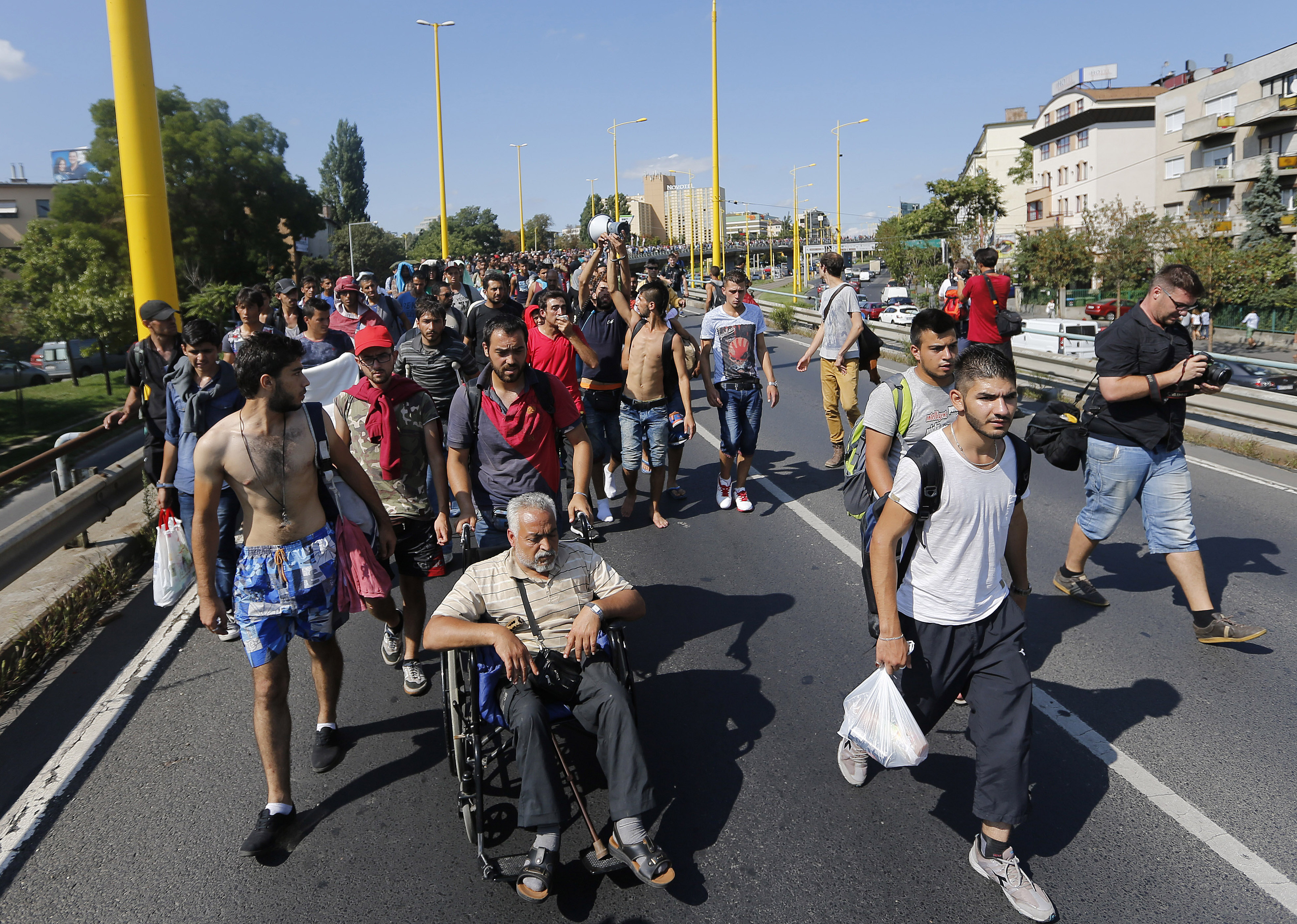 A large group of asylum-seekers walk  out of Budapest, Hungary, Friday, Sept. 4, 2015. Over 150,000 people seeking to enter Europe have reached Hungary this year, most coming through the southern border with Serbia, and many apply for asylum but quickly try to leave for richer EU countries.  Photo: AP