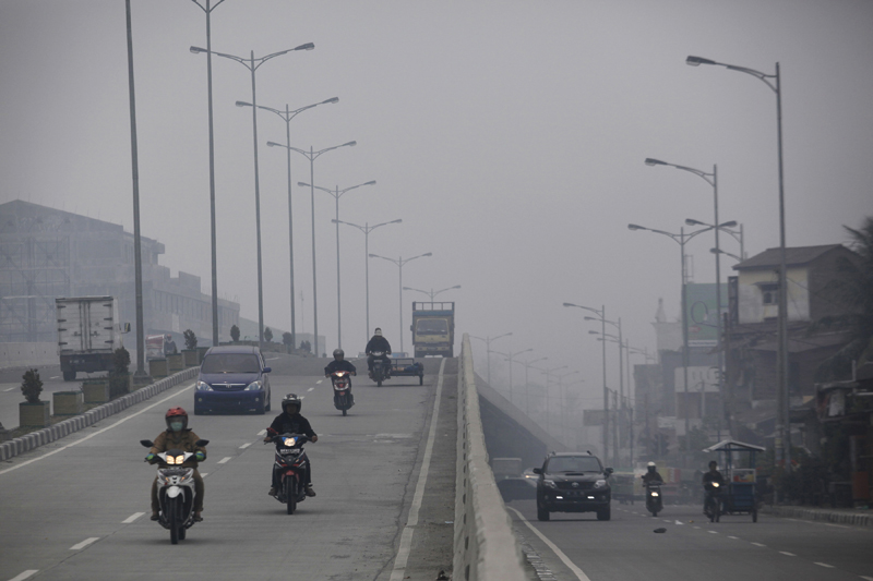 Motorists ride through the roads blanketed by haze from wildfires in neighboring province of Riau, in Medan, North Sumatra, Indonesia, Thursday, Sept. 3, 2015. Government negligence, rampant development and illegal land clearing, often combined, spark wildfires in Indonesian island of Sumatra and Borneo that annually ravage thousands of acres of forest and could cover parts of neighboring Malaysia and Singapore in a thick noxious haze. (AP Photo/Binsar Bakkara)