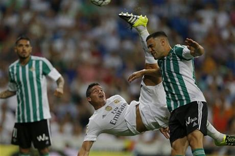 Real Madrid's James Rodriguez, centre, performs an overhead kick to score his side's fourth goal past Real Betis' Bruno Gonzalez, right, during a Spanish La Liga soccer match between Real Madrid and Real Betis at the Santiago Bernabeu stadium in Madrid, Saturday, Aug. 29, 2015. AP