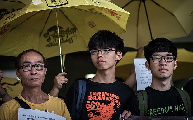 Student protesters Joshua Wong (centre L) and Nathan Law (R) stand outside the court of justice in Hong Kong.Photo: AFP