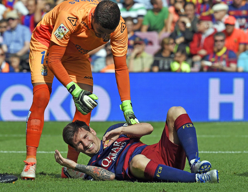 Barcelona's Lionel Messi (right) complains after being injured next to Las Palmas' ngoalkeeper Javi Varas during their Spanish League match at the Camp Nou Stadium in Barcelona on Saturday. Photo : AFP